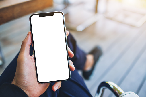 Mockup image of a man holding black mobile phone with blank white screen