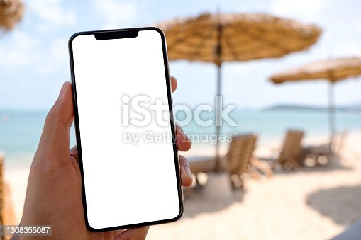 Mockup image of a man holding mobile phone with blank desktop screen while sitting on the beach