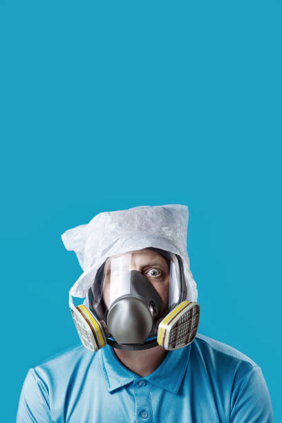 a man in a gas mask and a plastic bag on his head symbolizes the protection of the environment from pollution on blue background a man in a gas mask and a plastic bag on his head symbolizes the protection of the environment from pollution on a blue background irradiation stock pictures, royalty-free photos & images