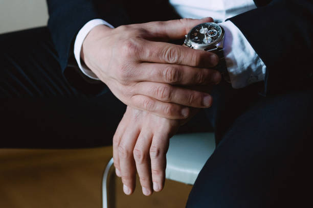 a man in a strict suit a man in a strict suit adjusts expensive watches on his hand luxury watch stock pictures, royalty-free photos & images