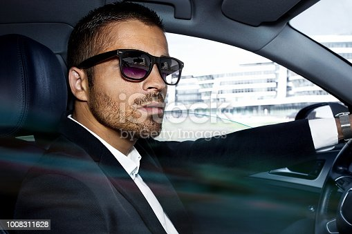handsome businessman is sitting in luxury car. Serious bearded man in suit is driving