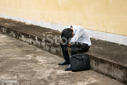 istock a man in formal outfit sitting hopeless on footpath 1162365690