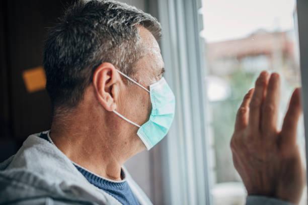 un uomo in isolamento a causa di un virus - hand on glass covid foto e immagini stock