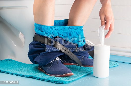 1045838148 istock photo a man in the bathroom, sitting on the toilet with his pants down and pulls wet wipes from the case 1127463843