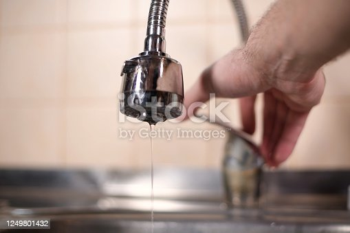 a man opens a faucet in the kitchen, but no water comes. Overlapping water, shutting off water supply. Close-up
