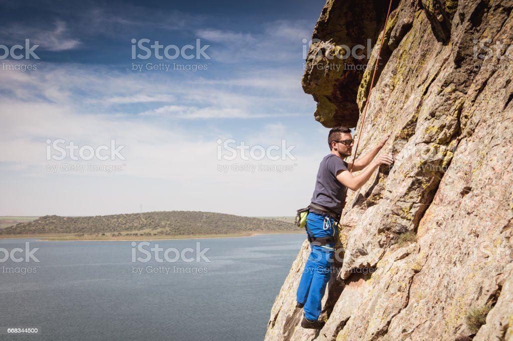 a man practicing climbing on rocks mountain stock photo