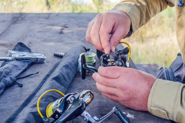 a man repairs a fishing reel with improvised means a man repairs a fishing reel with improvised means. fishing reel stock pictures, royalty-free photos & images
