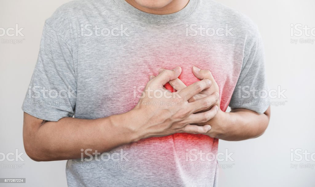 a man touching his heart, with red highlight of heart attack, heart failure and others heart disease stock photo