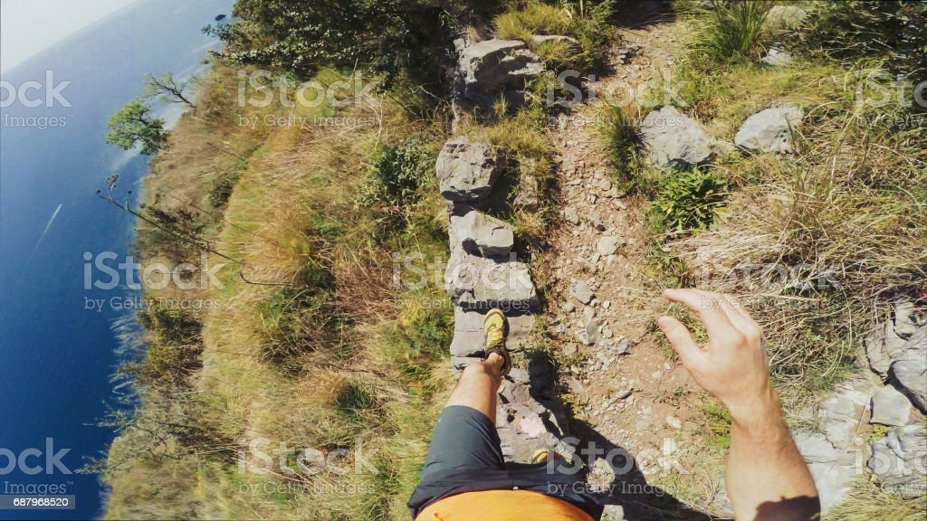 POV of a Man trail running on a single track on high cliff stock photo