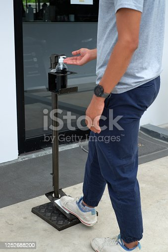 Close up picture of a man used foot operated hand sanitizer dispenser or hands free sanitizer stand at pubic area. Touchless equipment. cleaning and protect from Covid-19, Corona virus disease.