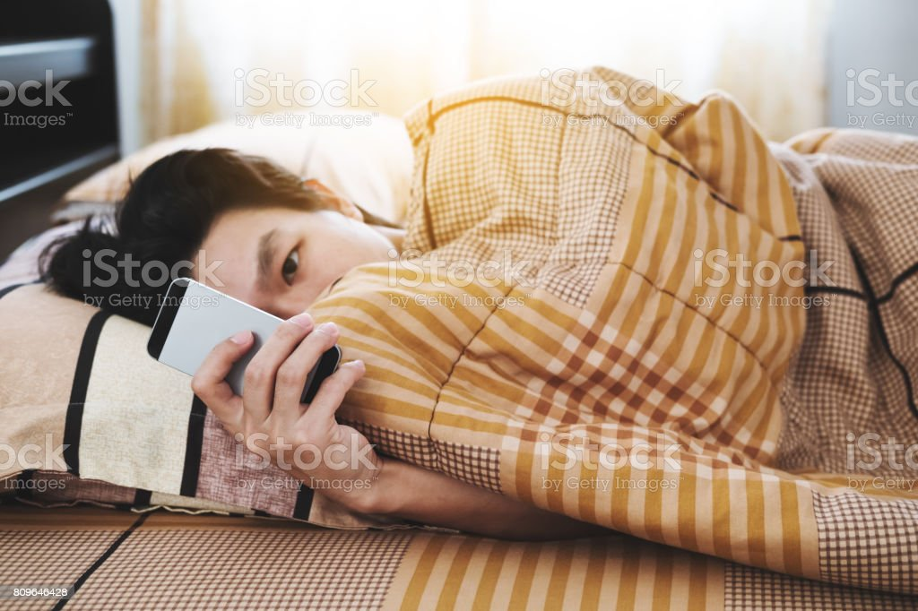 a man using smart phone in the morning, checking message after waking up stock photo