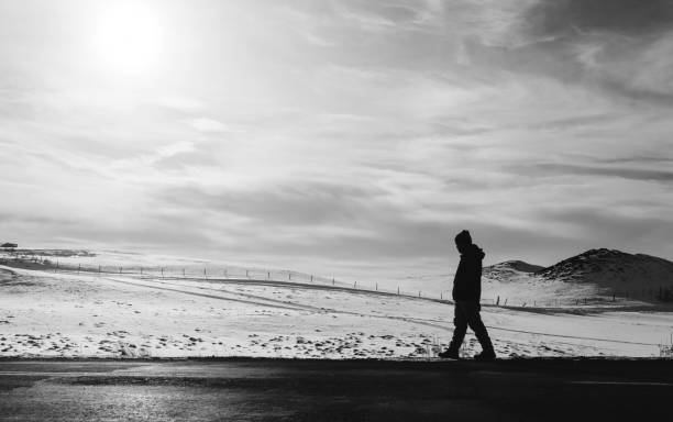 a man walking away on an empty desolated road - desolated stock pictures, royalty-free photos & images