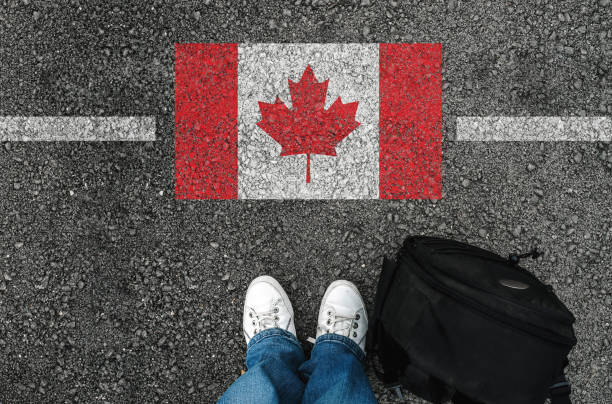 a man with a shoes is standing next to flag of Canada a man with a shoes and backpack is standing on asphalt next to flag of Canada and border canada stock pictures, royalty-free photos & images