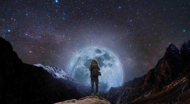 a man with backpack standing on mountain peak at night, and silhouette mountain with bright full moon and sky full of stars stock photo