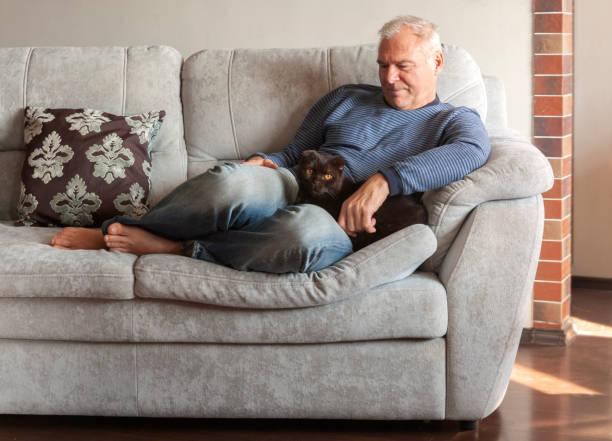 A man with his cat on the couch picture id1146194940?b=1&k=6&m=1146194940&s=612x612&w=0&h=dg19ntpwjizv d9ukbfm1zjdeq6lwjqp6lf0kh9jhkw=