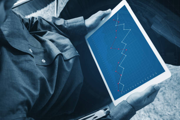 a man working on digital tablet, business decreasing graph on screen stock photo