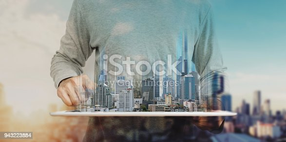 istock a man working on digital tablet, with Hologram futuristic modern buildings. City sunrise background 943223884