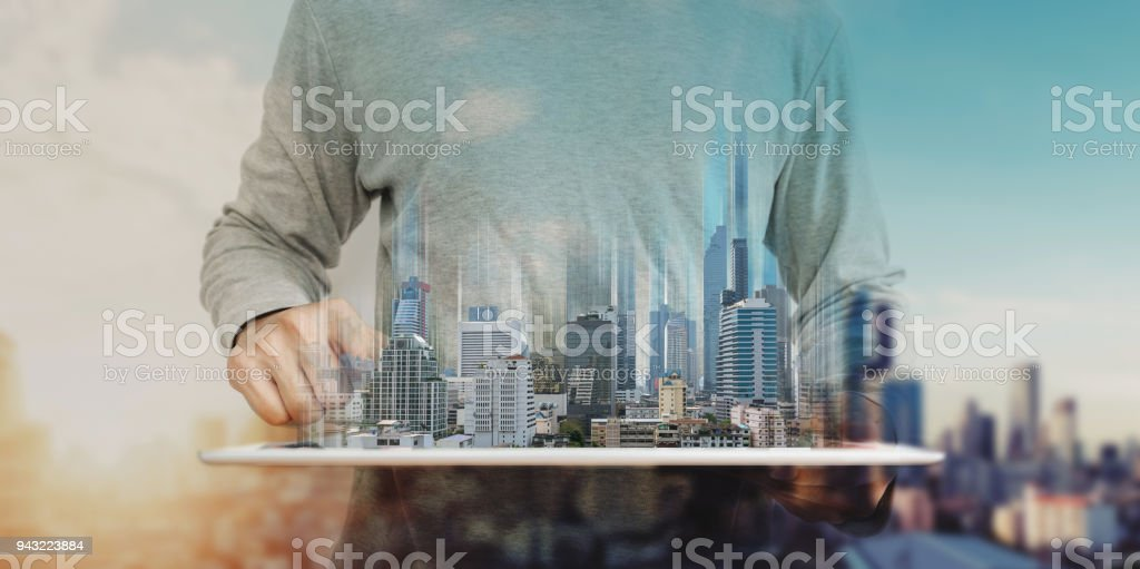 a man working on digital tablet, with Hologram futuristic modern buildings. City sunrise background stock photo