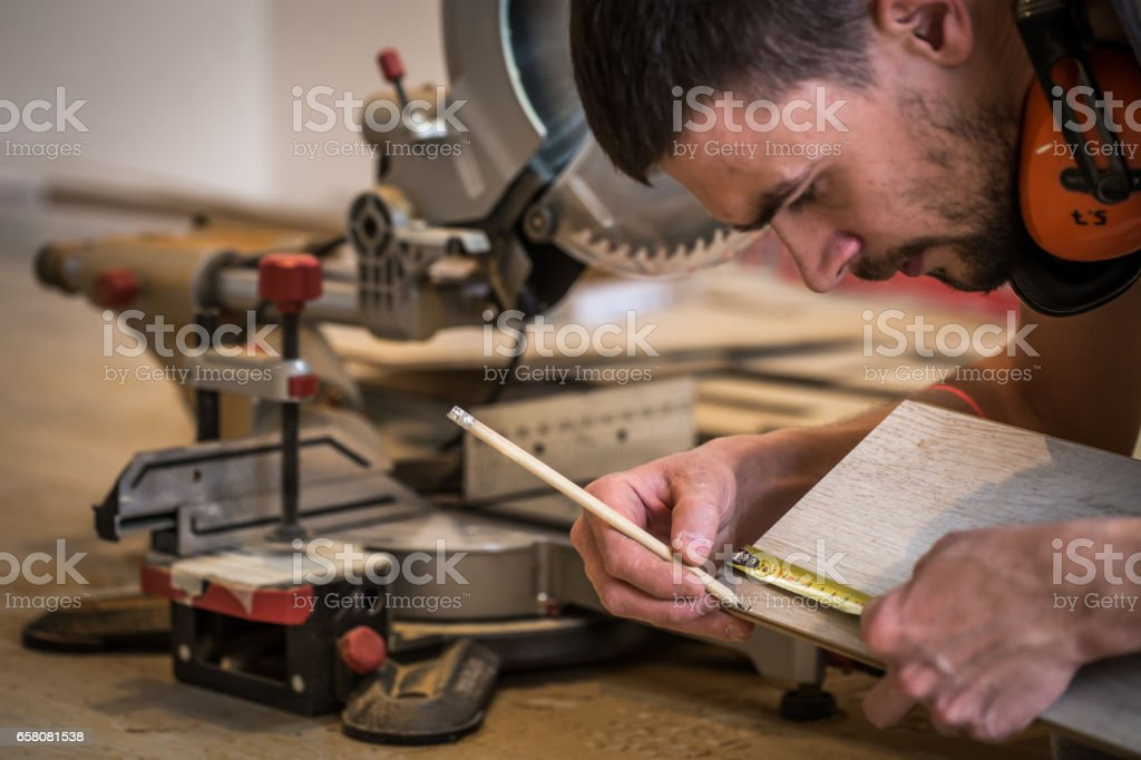 a man working with a miter saw royalty-free stock photo