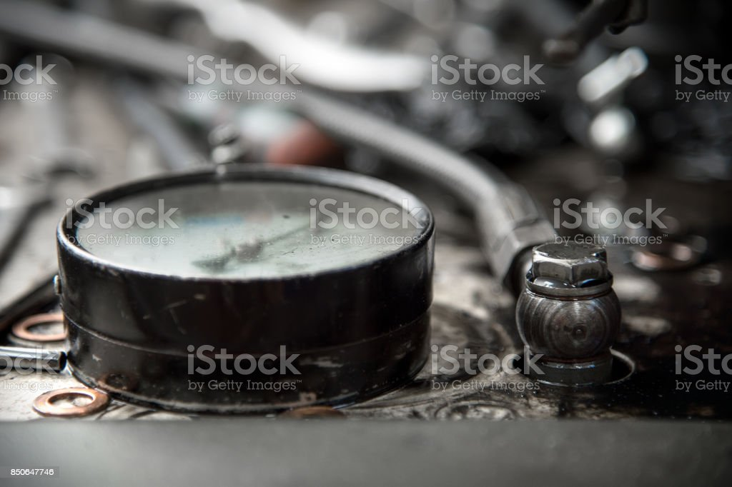 a manometer lies on a table next to high pressure hoses stock photo