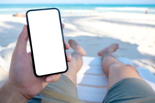 a man's hand holding black mobile phone with blank desktop screen - phone, travelling, copy space imagens e fotografias de stock