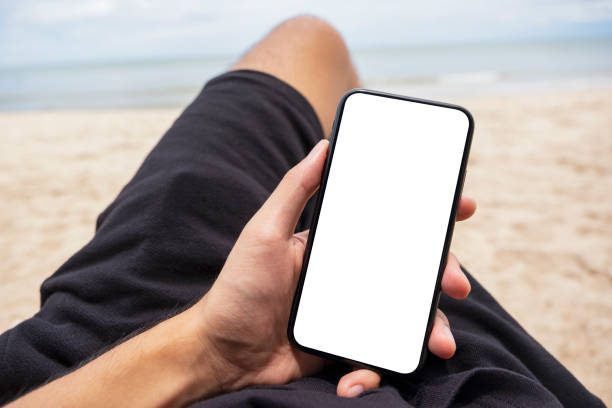 a man's hand holding black mobile phone with blank desktop screen while lying down on beach chair - phone, travelling, copy space imagens e fotografias de stock