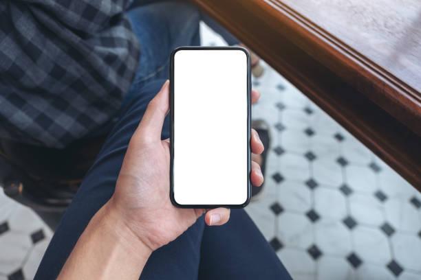 Die Hand eines Mannes, der weißes Handy mit leerem Desktop-Bildschirm hält – Foto