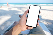 Mockup image of a man's hand holding white mobile phone with blank desktop screen while laying down on beach chair