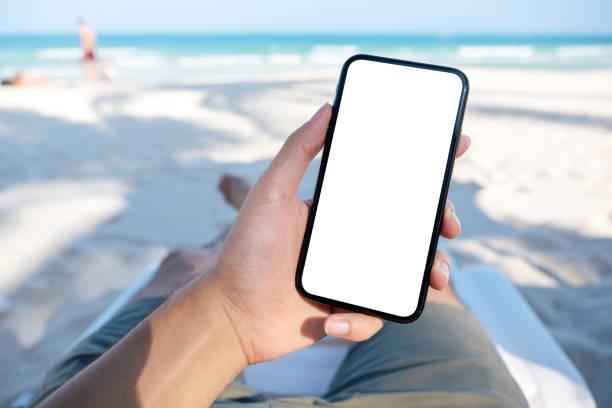 Die Hand eines Mannes hält weißes Handy mit leerem Desktop-Bildschirm, während sie sich auf den Strandstuhl legt – Foto