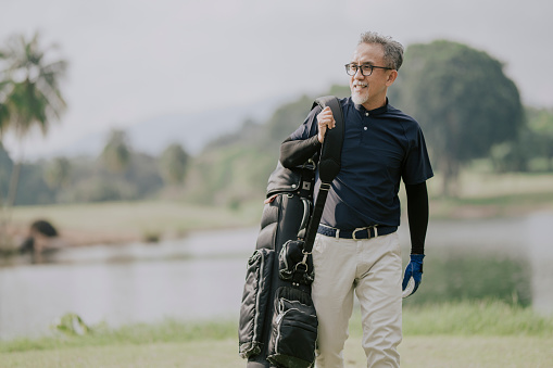 side view of a matured man golfer carrying a golf bag looking away in the golf course