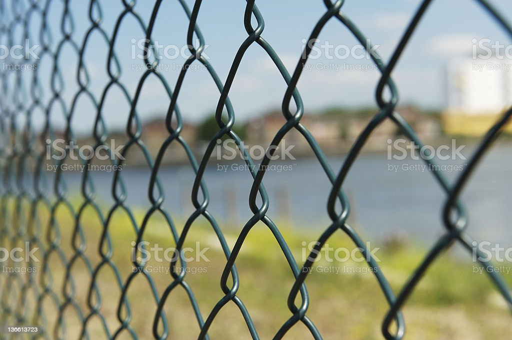 a metal link fence overlooking wearer and a coastline royalty-free stock photo