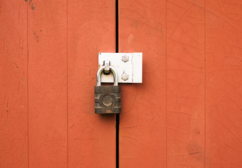 istock a metal padlock protecting locking two wooden doors outside 828656058