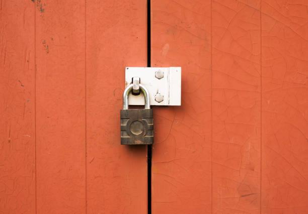 een metalen hangslot bescherming vergrendeling twee houten deuren buiten - hangslot stockfoto's en -beelden