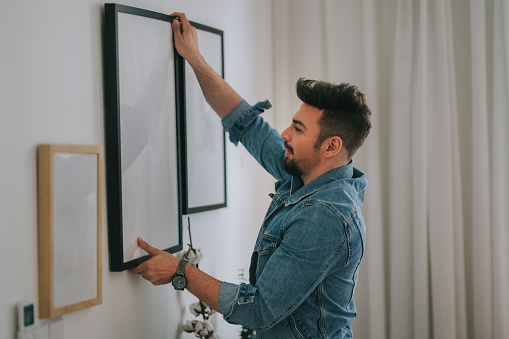 a middle eastern man with beard hanging a painting on the wall at his living room