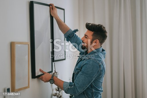 istock a middle eastern man with beard hanging a painting on the wall at his living room 1218482441