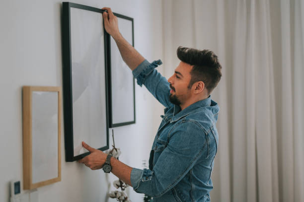 a middle eastern man with beard hanging a painting on the wall at his living room a middle eastern man with beard hanging a painting on the wall at his living room decorating stock pictures, royalty-free photos & images