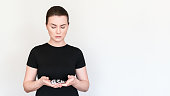 a model in a black T-shirt holds pills and capsules in blisters in her hands. Shot on a white background, place for text. Treatment Concept - Medication