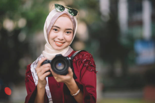 A modern asian malay muslim woman holding a dslr camera pointing at picture id1209464224?b=1&k=6&m=1209464224&s=612x612&w=0&h=bxj4ywubgjoigc2v5v1 uqhqtb0yt rmt2 qiz sz0y=
