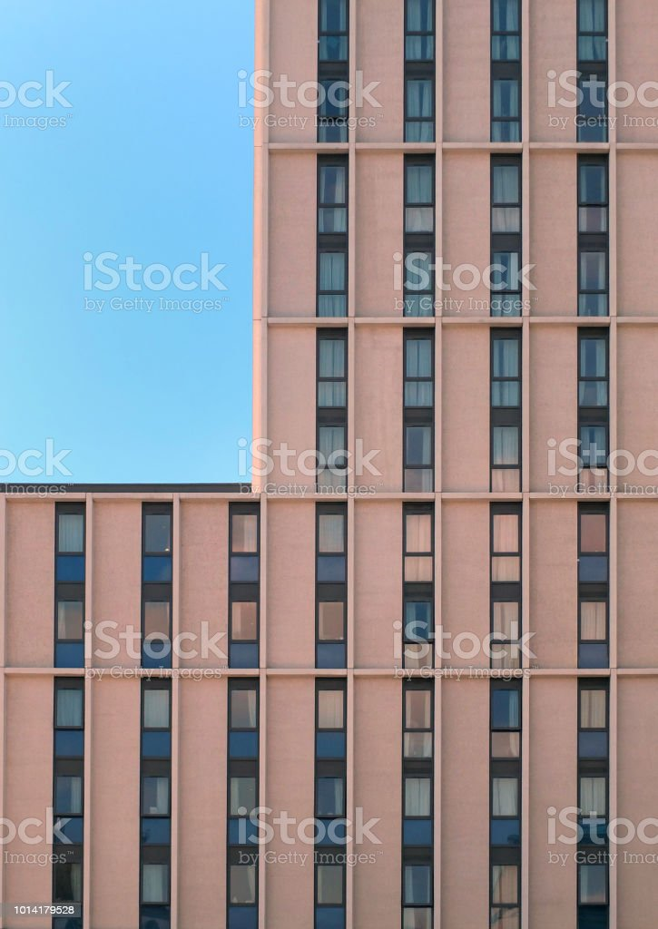 a modern concrete highrise concrete building with geometrical repeating windows with angular details and corner showing blue sky stock photo