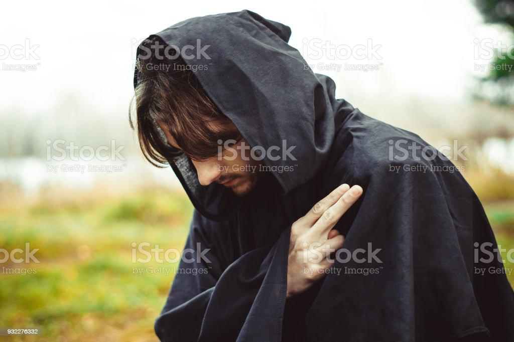um monge em vestes rezando na floresta - foto de acervo