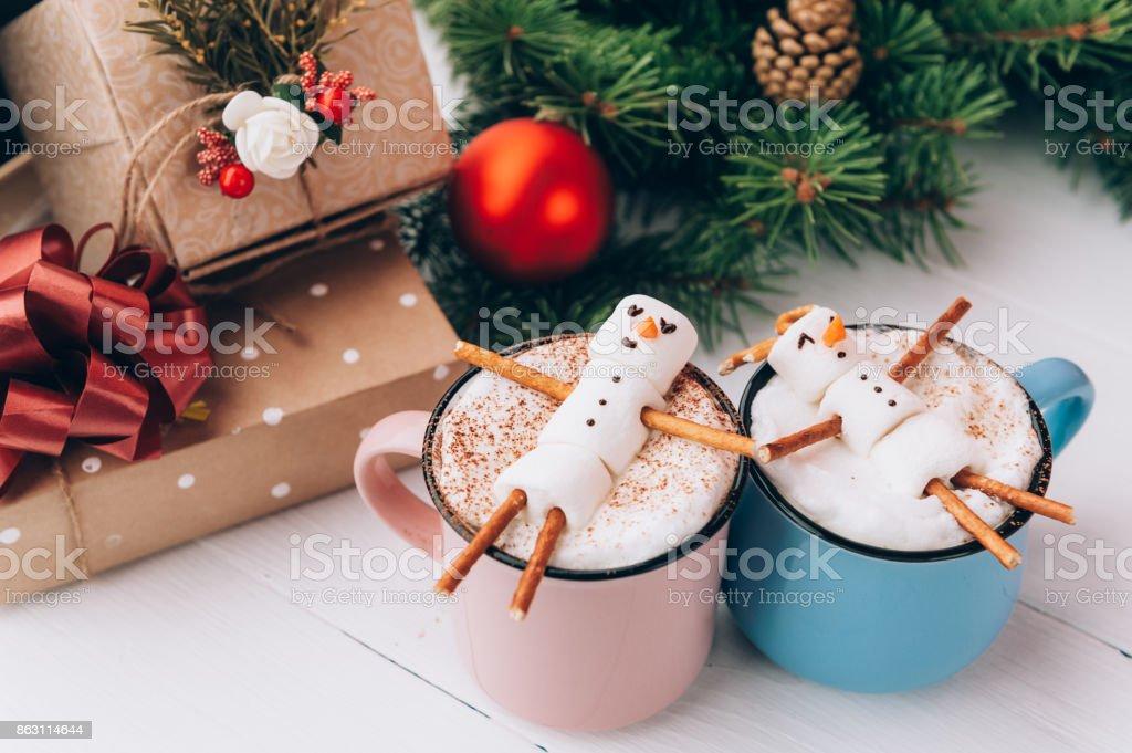 uma caneca com chocolate quente sobre uma mesa de madeira com um homem de marshmallow que está descansando em uma caneca - foto de acervo