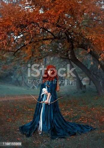 istock a mysterious red-haired warrior girl stands guard over her land, a elven princess holds a bow and arrows, preparing for battle, an attractive woman in a misty forest alone, gothic style, cool colors 1168155959