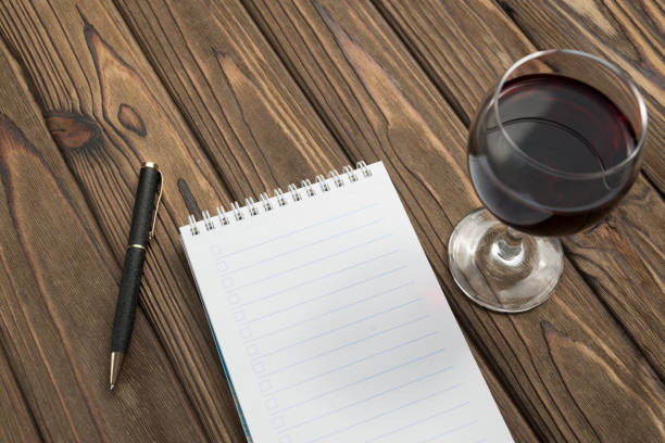 a notebook on a spiral, a ballpoint pen, a glass of red wine on a wooden table background. stock photo