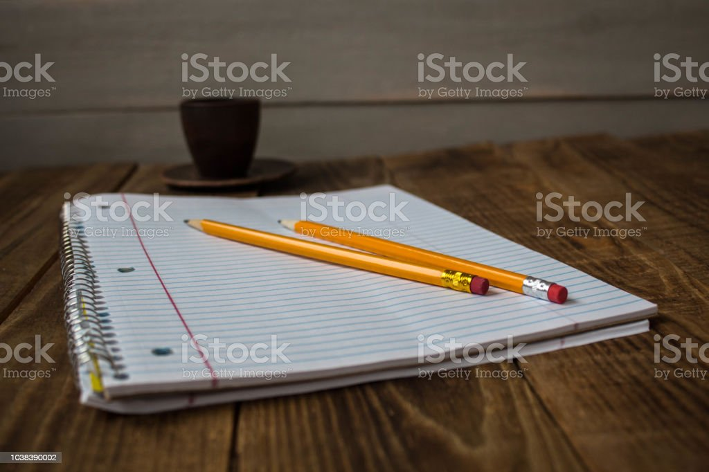 a notepad with pencils and cup of tea on wooden background stock photo