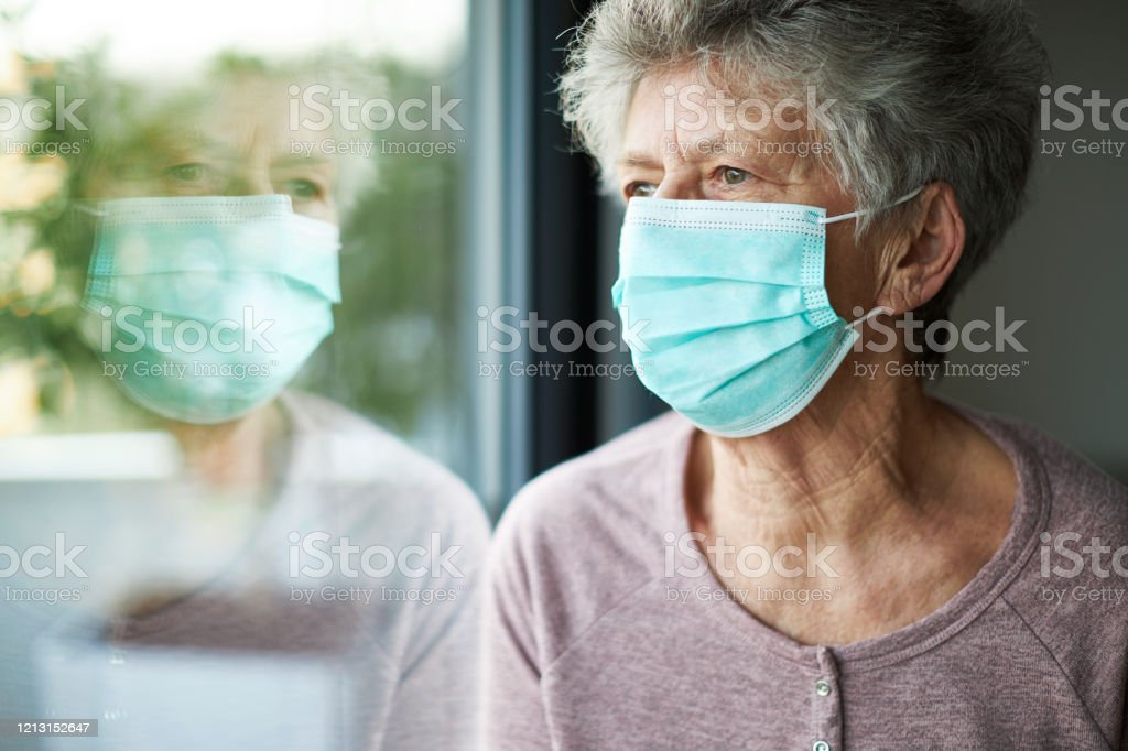 a old woman or grandma is wearing a respirator or surgical mask and looking out of the window a old woman or grandma is wearing a respirator or surgical mask and is looking out the window while she is in quarantine because of the corona virus Adult Stock Photo