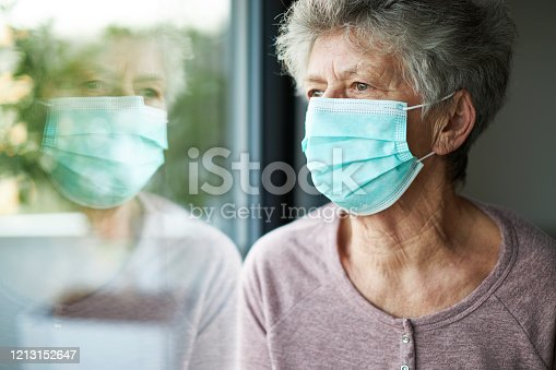 a old woman or grandma is wearing a respirator or surgical mask and is looking out the window while she is in quarantine because of the corona virus