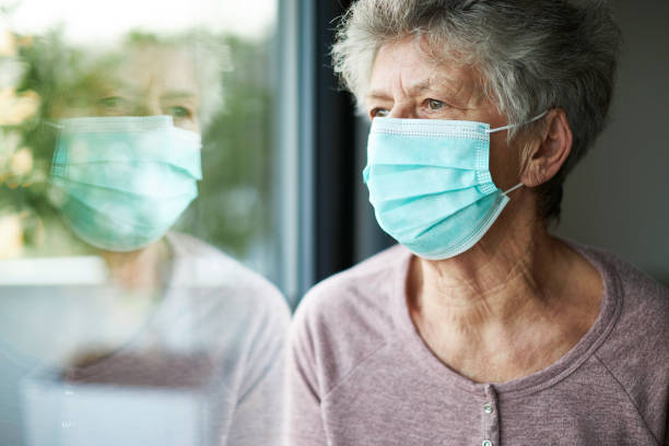 a old woman or grandma is wearing a respirator or surgical mask and looking out of the window a old woman or grandma is wearing a respirator or surgical mask and is looking out the window while she is in quarantine because of the corona virus quarantine stock pictures, royalty-free photos & images