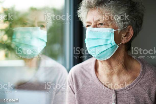 A Old Woman Or Grandma Is Wearing A Respirator Or Surgical Mask And Looking Out Of The Window Stock Photo - Download Image Now