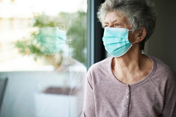a old woman or grandma is wearing a respirator or surgical mask and looking out of the window a old woman or grandma is wearing a respirator or surgical mask and is looking out the window while she is in quarantine because of the corona virus avoidance stock pictures, royalty-free photos & images