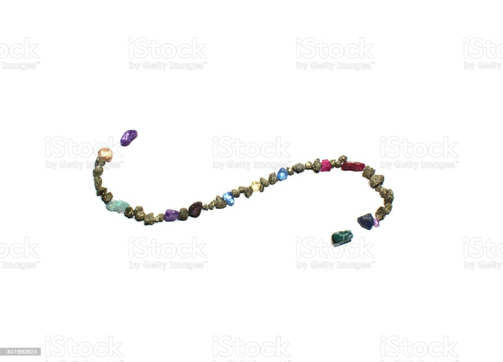 a page divider swirl symbol made from gold, blue and red shiny rocks and gems. The picture is reflective of color, texture, symbols, separated, white stock photo